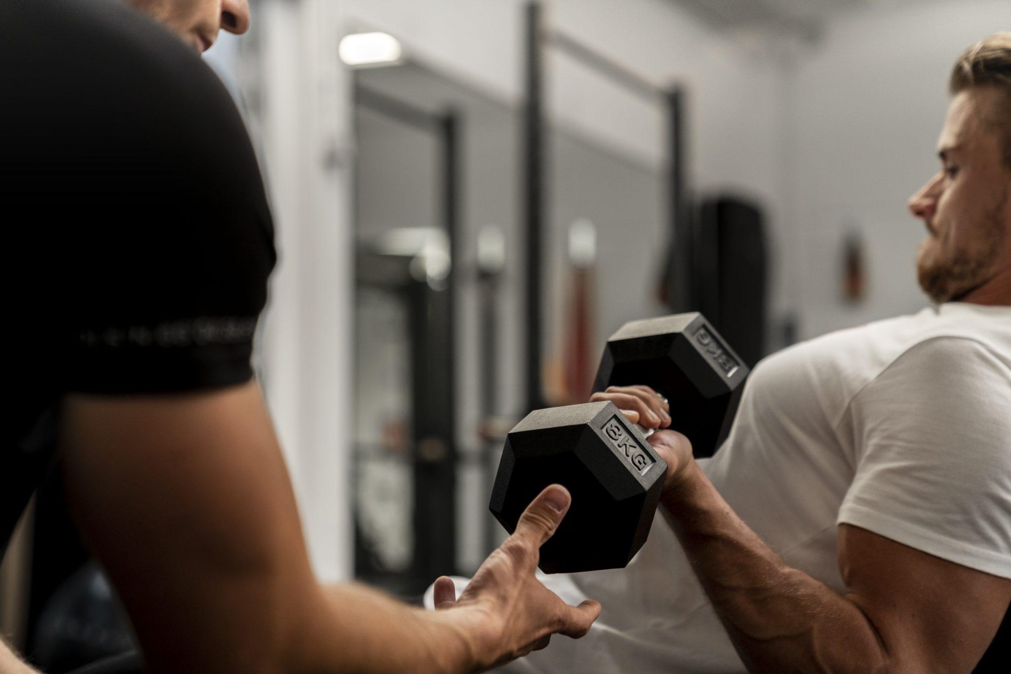 trainer Joshua helpt een klant tijdens een personal training sessie